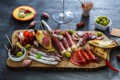 不同的快餐和开胃菜的混合 在黑石背景的西班牙塔帕纤维布 棒 文本的空间 熟食店 免版税库存照片
