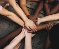 不同的手是一起加入在木桌上 免版税库存照片