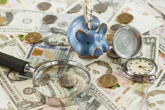 不同的收藏家` s硬币和钞票与一个存钱罐和时钟 免版税库存图片