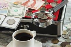 不同的收藏家` s硬币和钞票与一个放大镜、箱子硬币的和咖啡 免版税库存照片