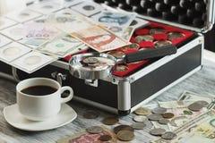 不同的收藏家` s硬币和钞票与一个放大镜、箱子硬币的和咖啡 库存照片