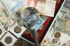 不同的收藏家` s硬币和钞票与放大镜 库存图片