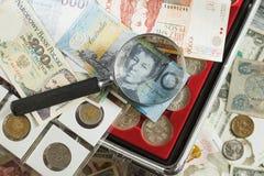 不同的收藏家` s硬币和钞票与放大镜 免版税库存照片