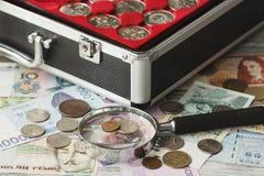 不同的收藏家` s硬币和钞票与放大镜 库存照片