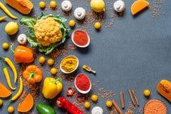 不同的新鲜的五颜六色的有机菜和香料 在灰色背景的健康未加工的素食主义者食物与赠送阅本空间 库存图片