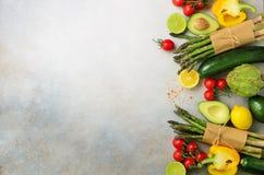 不同的有机菜-芦笋,蕃茄樱桃,鲕梨,朝鲜蓟,胡椒,石灰,柠檬,在灰色的盐 库存图片