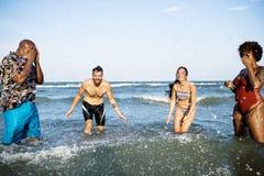 不同的朋友获得乐趣在海滩 免版税图库摄影