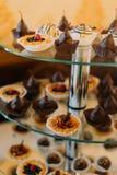 不同的杯形蛋糕的特写镜头视图装饰用果子和在玻璃点心安置的焦糖调味汁站立 库存照片