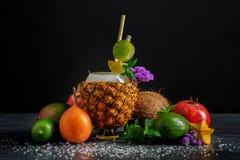 不同的热带水果 菠萝杯子、成熟鲕梨、石榴石和椰子在黑背景 夏天成份 库存图片