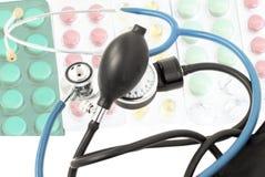 以不同的片剂为背景的蓝色听诊器 免版税库存图片