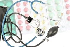 以不同的片剂为背景的蓝色听诊器 免版税图库摄影