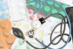 以不同的片剂为背景的蓝色听诊器 库存图片