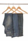 不同的牛仔裤在挂衣架。 免版税库存图片