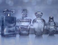 不同的瓶在蓝色背景的香水 免版税库存照片