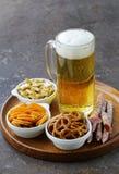 不同的盐味的快餐和一杯新鲜的啤酒 免版税库存照片