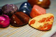 不同的矿物和结构各种各样次贵重的石头在一张木桌上 被擦亮的一汇集的各种各样 库存照片