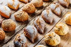 不同的种类在木桌上的新鲜面包 面包的被隔绝的分类在棕色背景的 库存图片