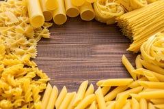 不同的种类在木背景的面团 Farfalle、意大利细面条、面条、fusilli和penne rigate 鲜美意大利烹调 库存图片