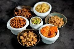 不同的种类快餐-芯片、盐味花生、腰果、杏仁和开心果,与盐的椒盐脆饼,土豆,盐味的秸杆 库存照片