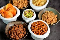 不同的种类快餐-芯片、盐味花生、腰果、杏仁和开心果,与盐的椒盐脆饼,土豆,盐味的秸杆 库存图片