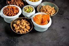 不同的种类快餐-芯片、盐味花生、腰果、杏仁和开心果,与盐的椒盐脆饼,土豆,盐味的秸杆 免版税图库摄影