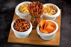 不同的种类快餐-芯片、盐味花生、腰果、杏仁和开心果,与盐的椒盐脆饼,土豆,盐味的秸杆 免版税库存图片