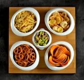 不同的种类快餐-芯片、盐味花生、腰果、杏仁和开心果,与盐的椒盐脆饼,土豆,盐味的秸杆 免版税库存照片