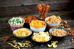 不同的种类快餐-芯片,盐味花生,腰果,与山葵的豌豆,与盐的椒盐脆饼,土豆,盐味的秸杆 库存图片