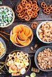 不同的种类快餐-芯片,盐味花生,腰果,与山葵的豌豆,与盐的椒盐脆饼,土豆,盐味的秸杆 图库摄影