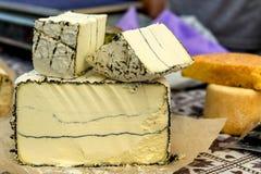 不同的种类整个和被刻凹痕的头在市场c上的乳酪 免版税库存照片