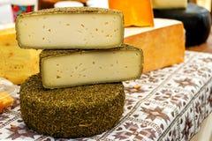 不同的种类整个和被刻凹痕的头在市场c上的乳酪 免版税库存图片