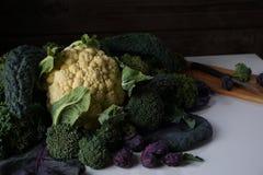 不同的种类静物画在桌上的圆白菜:Lacinato无头甘蓝,蓝色卷曲了Vates无头甘蓝,花椰菜,抱子甘蓝末端增殖比 图库摄影