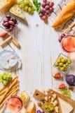 不同的种类乳酪、酒和快餐在木的白色 库存图片