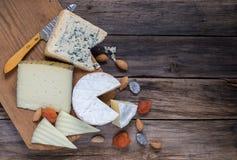 不同的种类在老木桌上的乳酪 免版税图库摄影