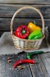 不同的种类胡椒在一张木桌上和在篮子 库存照片