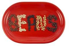 不同的种类豆在红色盘,孤立的 库存图片