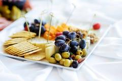 不同的种类酒快餐:乳酪、薄脆饼干、果子和橄榄在白色桌上 库存照片