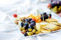 不同的种类酒快餐:乳酪、薄脆饼干、果子和橄榄在白色桌上 免版税库存图片
