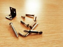 不同的紧固件和硬件谎言在轻的木纹理与自动攻丝螺杆、钥匙和家具领带 免版税库存图片