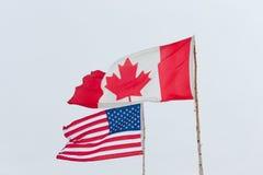 不同的美国和加拿大的旗子幽暗的背景的 库存图片