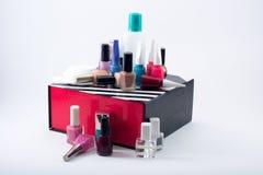 不同的色的指甲油和化装棉在一个黑/白色/红色箱子 免版税库存照片