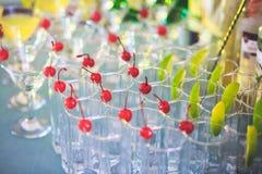 不同的色的鸡尾酒美好的线在党、龙舌兰酒、马蒂尼鸡尾酒,伏特加酒和其他的在装饰的承办的花束桌上 库存照片