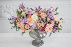 不同的花华美的花束  在葡萄酒金属花瓶的植物布置 制表设置 丁香和桃子颜色 库存照片