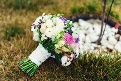 不同的花新娘花束包裹了在绿草的鞋带丝带 免版税库存图片
