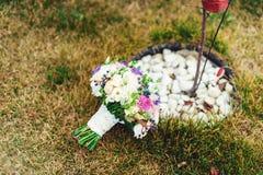 不同的花新娘花束包裹了在绿草的鞋带丝带 图库摄影