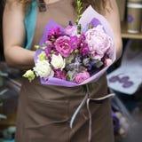 不同的花现代时兴的花束特写镜头在做在商店的无法认出的女孩卖花人的手上 免版税图库摄影