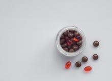 不同的药片溢出在轻的表面上的一个玻璃瓶子外面 免版税库存照片