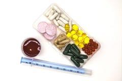 不同的药片,疗程,在箱子的药片与医学的药物特写镜头的与在白色背景的一个注射器 免版税库存照片