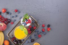 不同的莓果和果子在灰色背景、汁液从新鲜水果,酸奶和莓果早餐维生素和戒毒所的 库存图片