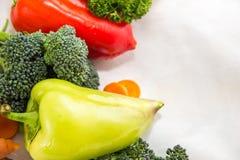 不同的菜和新鲜的草本在白色桌上 黄色胡椒,橙色切片红萝卜 库存图片